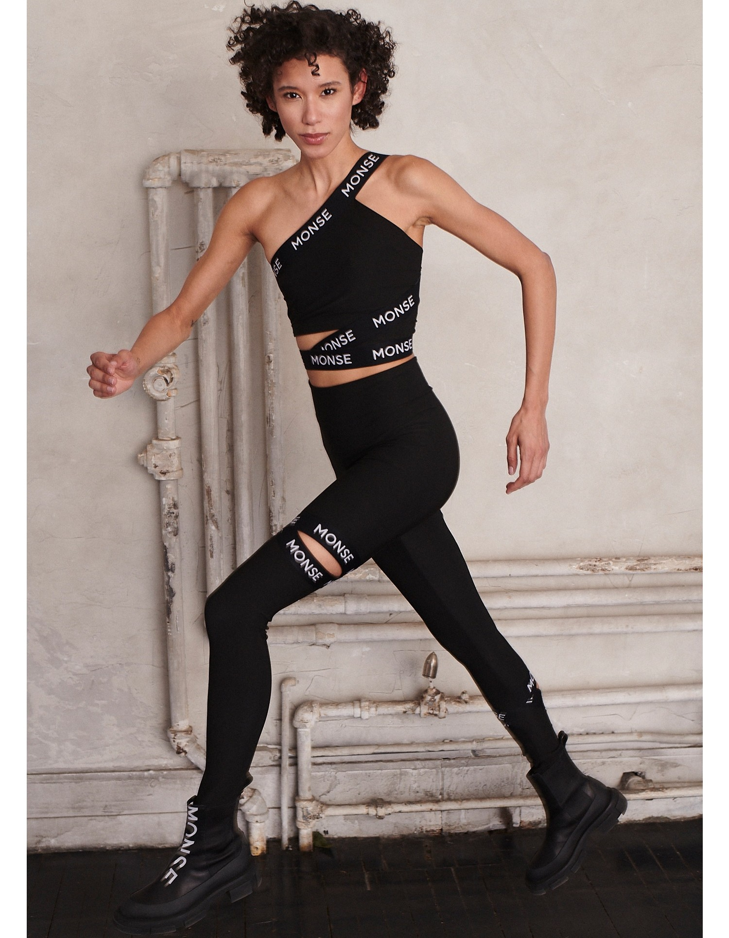 MONSE Cut Out Leggings in Black on Model Running Front Side View